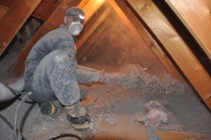 man installing blown cellulose insulation